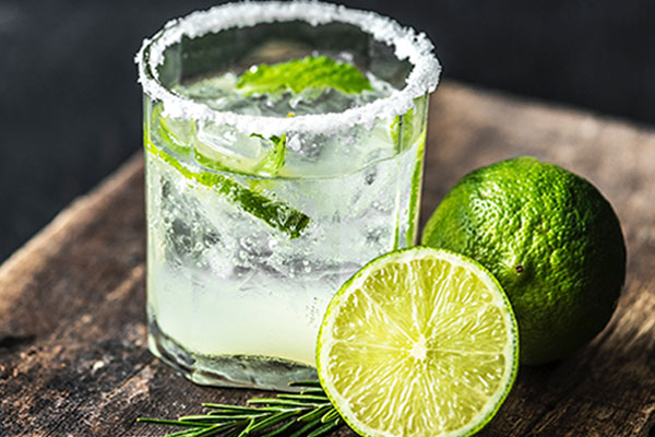 short glass with salt on rim and limes to the side