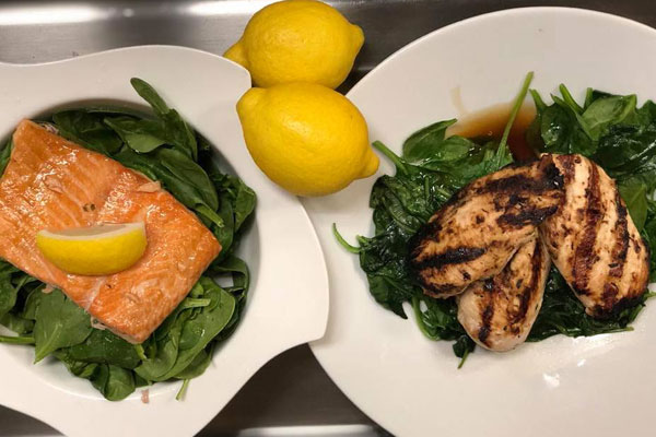 salmon and chicken on white plates with lemons